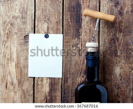 open glass bottle with a corkscrew in the cover against the background of boards and a blank sheet of paper.close-up