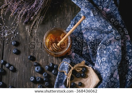 Open glass jar of liquid honey with honeycomb and honey dipper inside, fresh blueberries and bunch of dry lavender over old wooden table with blue textile rag. Dark rustic style. Top view - stock photo