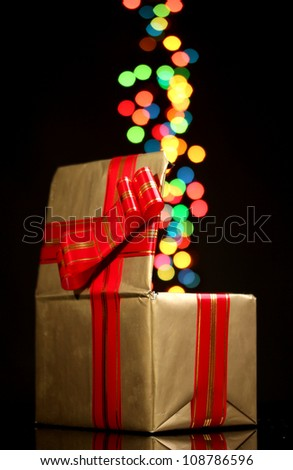 open golden gift box with bokeh background on black - stock photo