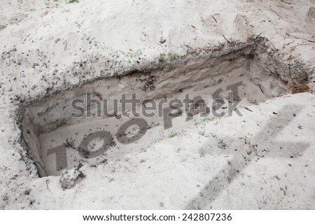 Open grave in the desert. In  the sand are written the words too fast. Concept for danger caused by driving too fast - stock photo