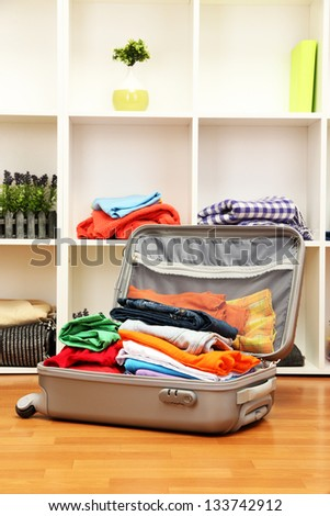Open grey suitcase with clothing in room - stock photo