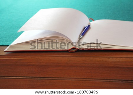 Open guestbook on the table with green cloth - stock photo