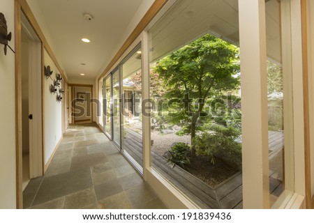 Open hallway with glass front and gorgeous Japanese Zen garden - stock photo