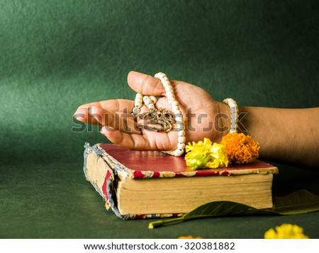 open hand showing Aum locket with beads, rested on a hindu scripture or book on green background, side angle - stock photo