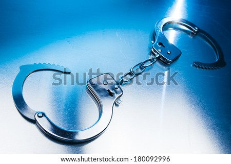 Open handcuffs, liberty concept on a metallic background and dramatic lighting - stock photo