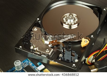 Open hard drive on a black wooden background. Production of computers. Electronics store. Backing up data on your computer. Modern technology. Place for your text. - stock photo