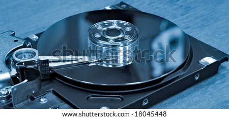 Open hard drive on office table. Blue toned. - stock photo