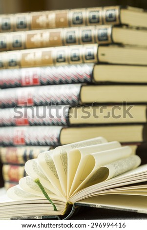 Open hardcover book with decorative folded pages arranged in a radiating fan lying on a table in front of a stack of leather bound gilt tooled books - stock photo