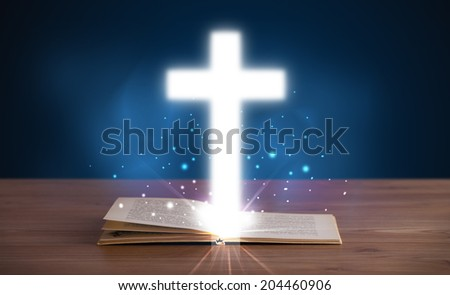 Open holy bible with glowing cross in the middle on wooden deck - stock photo