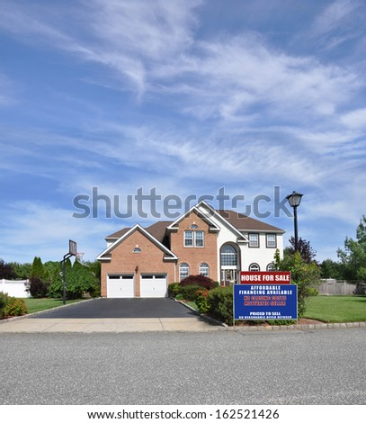 Open House Real Estate Sign Brick Suburban McMansion Home Two Car Garage Residential Neighborhood Street Blue Sky Clouds USA - stock photo