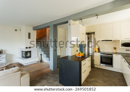 Open kitchen and living room in luxury house - stock photo