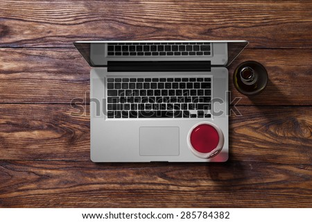 Open laptop and glass of red wine and bottle on brown wooden table. Top view - stock photo