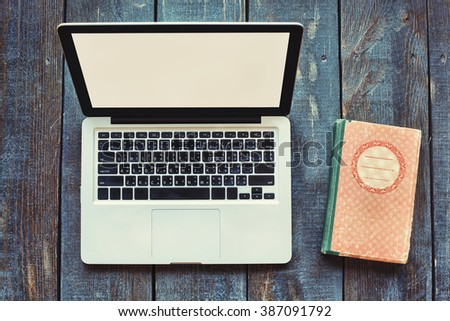 Open Laptop Computer and old book on wooden background - stock photo