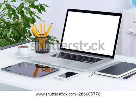 Open laptop mockup with digital tablet and smartphone on the office desk workspace. Consists of laptop, tablet computer, smartphone, notebook, cup of coffee. All devices in full focus. - stock photo