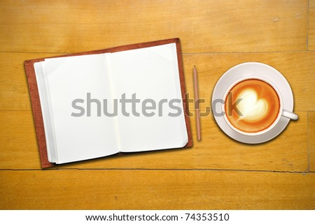 Open leather book with blank page, coffee and pencil on old wooden table - stock photo