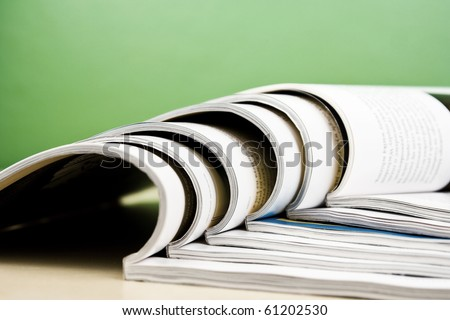 Open magazines in composition lying on table on green background - stock photo