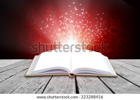 Open magic book on red Christmas background