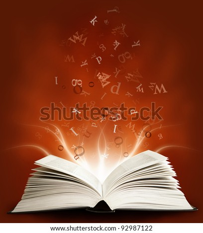 Open magic book with the letters on a red background and lights - stock photo