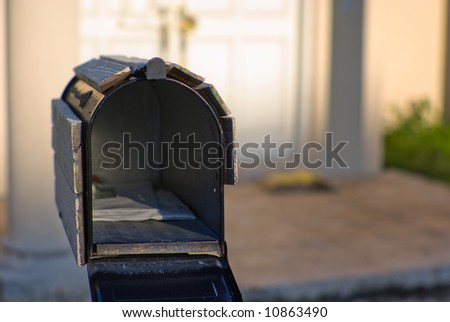 Open mailbox in front of abandoned house. - stock photo