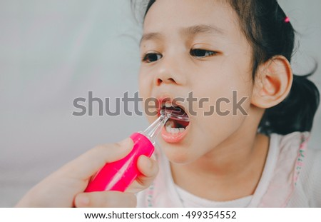 Open mouth of young girl during checking tooth and by dental mirror tools toy. Healthcare And Medicine Concept.