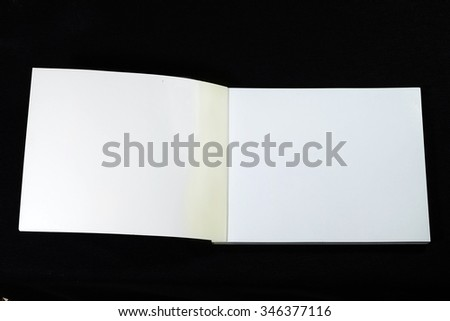 Open note book double page spread with blank pages on black background - stock photo