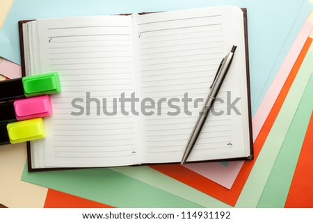 Open note book with lined pages free date space and ballpoint pen and markers. - stock photo