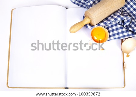 Open notebook and Basic baking ingredients - stock photo