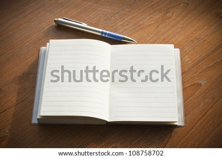 Open Notebook and Pen On Wooden Table - stock photo