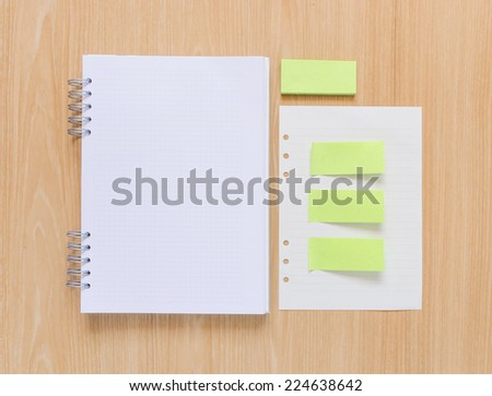 Open notebook, green paper stick and white paper sheet on wooden background. - stock photo