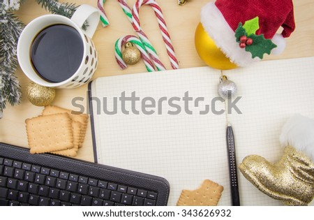 Open notebook, keyboard with cup of coffee and winter festive ornaments. - stock photo