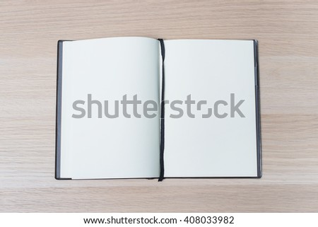 Open notebook on a wooden table, top view - stock photo