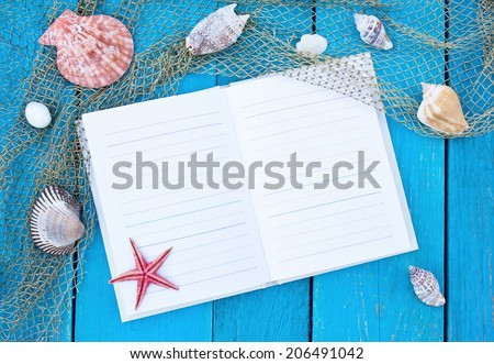 Open notebook on old blue wooden table with fishing net, cockleshells and red starfish - stock photo