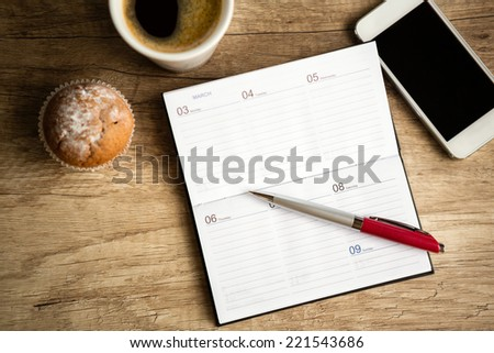 Open notebook on wooden desk, planning workweek - stock photo