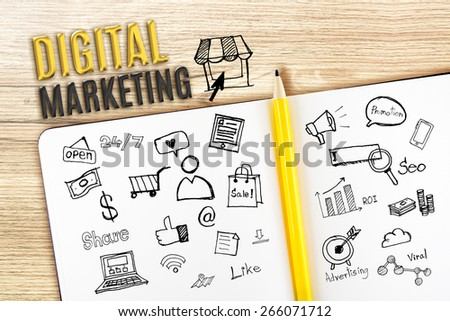 Open Notebook on wooden desk with icon relate with Digital Marketing, Business concept. - stock photo