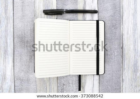 Open notebook with a black pen on a white wooden background. Top view - stock photo