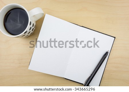 Open notebook with black pen and a cup of coffee, on wooden surface. - stock photo