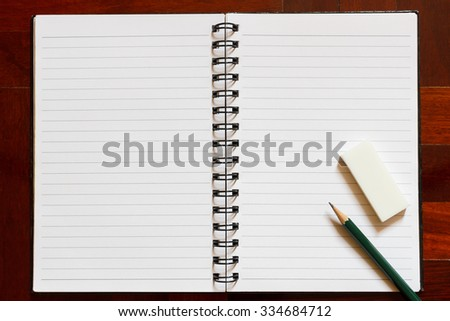 Open notebook with blank page and pencil and eraser. Wooden floor in the background.
