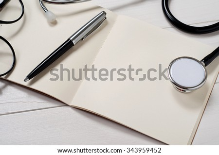Open notebook with blank pages with stethoscope, pen and stylish sunglasses on a white table closeup . Free space for text. Copy space. Top view - stock photo
