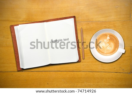 Open notebook with cup of coffee - stock photo