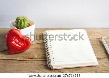 Open notebook with red heart and pen with cactus on wooden board background. Concept of Valentine Day.