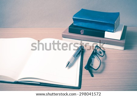 open notebook with stack of book on wood background vintage style