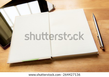 Open notebook with tablet and pen on wood board - stock photo