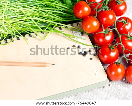 open notebook  with tomatoes, chives and spices