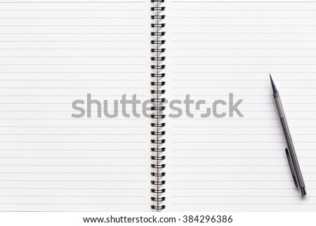 Open notebook with white lined pages and pencil on book