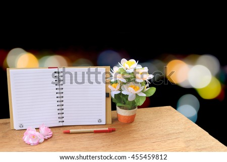 open notepad and flower vase on blur bokeh light in city background - stock photo