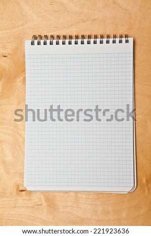 open notepad with spiral on a wooden background