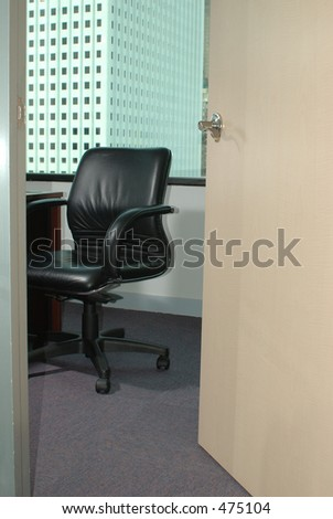 Open office door revealing a leather chair