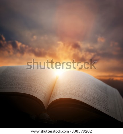 Open old book, light from the sunset sky, heaven. Fantasy, imagination, education, religion concept.  - stock photo