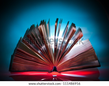 Open old book, mystical  light at background - stock photo