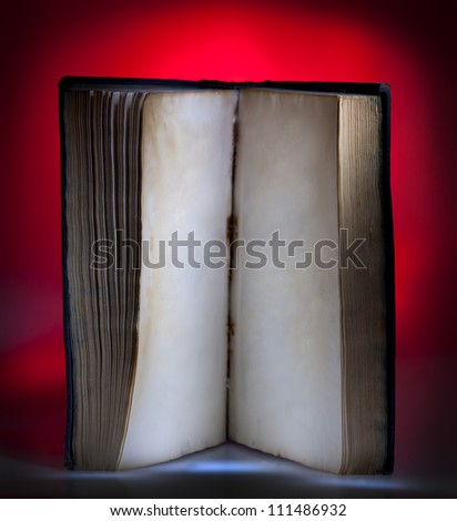 Open old book, mystical red light at background - stock photo